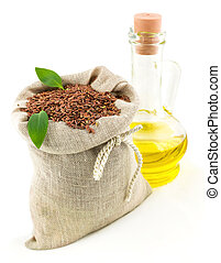 Sack of flax seeds and glass bottle of oil with leaves -...