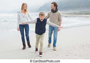 Happy family of three at the beach