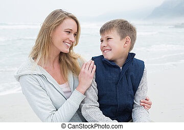 Cute boy with mother at beach