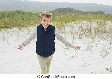 Cheerful young boy running at beach
