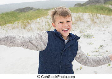 Cheerful boy running at beach