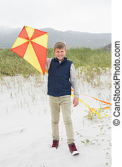 Portrait of a happy boy with kite at beach - Full length...