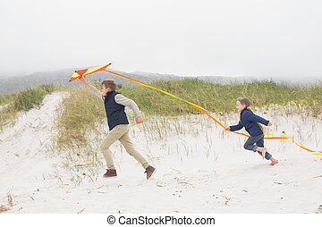 Cheerful kids running with kite at beach