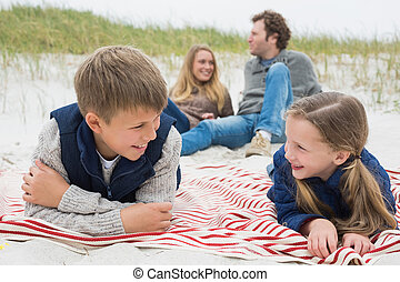 Happy family of four at a beach pic - Happy siblings lying...