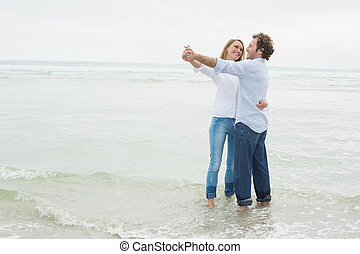 Full length of a couple dancing at beach - Full length of a...