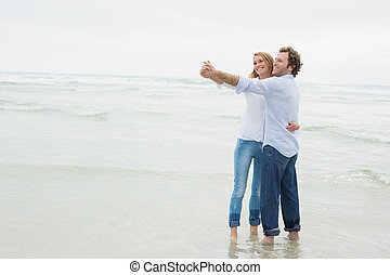 Young couple dancing at beach - Full length of a young...