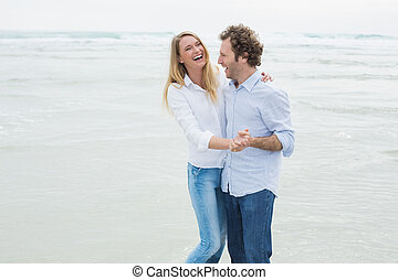 Cheerful couple dancing at beach