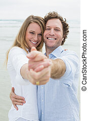 Happy young couple dancing at beach - Portrait of a happy...