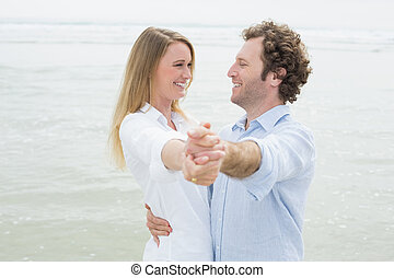 Happy young couple dancing at beach - Side view of a happy...