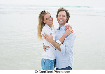 Happy romantic couple embracing at beach