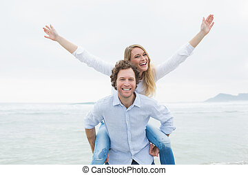 Man piggybacking woman at beach - Portrait of a young man...