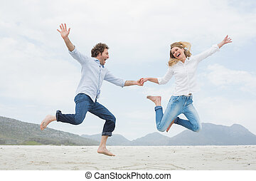 Cheerful couple holding hands and jumping at beach