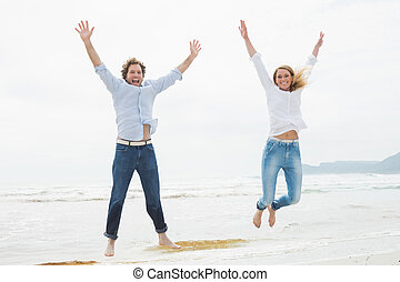 Cheerful young couple jumping at beach