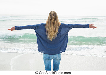 Rear view of a blond with arms outstretched at beach - Rear...