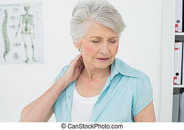 Senior woman suffering from neck pain with eyes closed in...