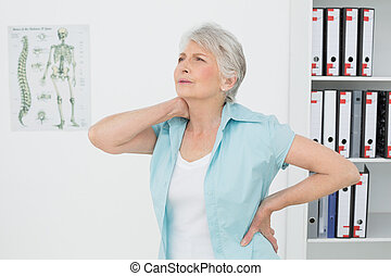 Senior woman suffering from neck pain in medical office -...