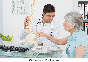 Male doctor explaining the spine to a senior patient in...