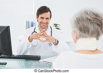 Smiling doctor listening to senior patient at medical office...