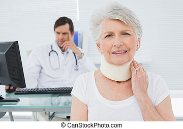 Senior patient in surgical collar with male doctor sitting at desk in background at medical office