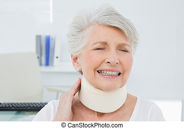 Senior woman wearing cervical collar with eyes closed -...