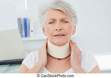 Senior woman wearing cervical collar in medical office -...