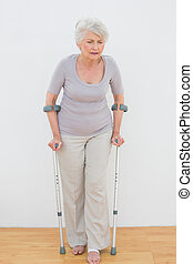 Full length of a senior woman with crutches standing against...