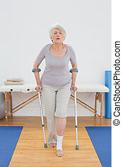 Full length of a senior woman with crutches in hospital gym...