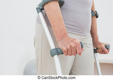 Close-up mid section of a woman with crutches standing...