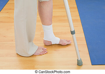 Low section of a woman with crutch and bandaged leg -...