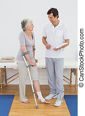 Therapist discussing reports with a disabled senior patient...