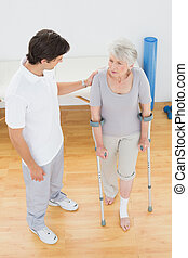 Male therapist in discussion with a disabled senior patient...