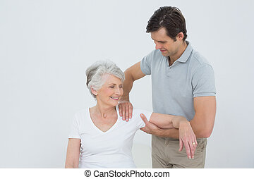 Physiotherapist massaging a smiling senior woman's arm -...