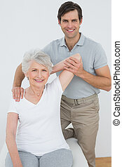 Physiotherapist stretching a smiling senior womans arm -...