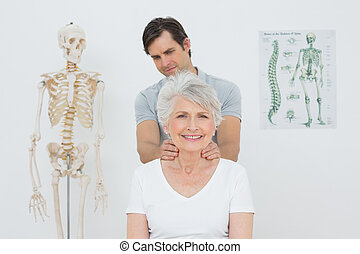 Male physiotherapist massaging a senior womans neck in the...