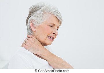 Side view of a senior woman suffering from neck pain -...