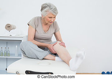 Senior woman with her hands on a painful knee while sitting...
