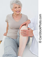 Displeased senior woman getting her knee examined at the...