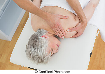 Physiotherapist massaging a senior woman's back - High angle...