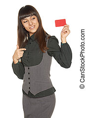 Smiling business woman holding credit card pointing at it,...