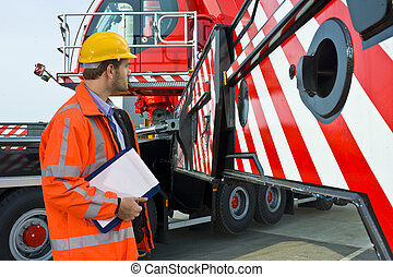 Crane supervisor - A man, wearing safety gear, inspecting...