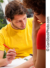 Students studying - Students in colorful t-shirts are...