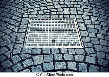 Paving stones with metal manhole