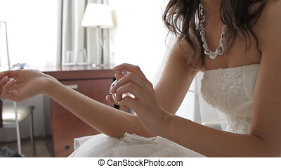 Woman spraying perfume on her wrist. Focus on hands and...