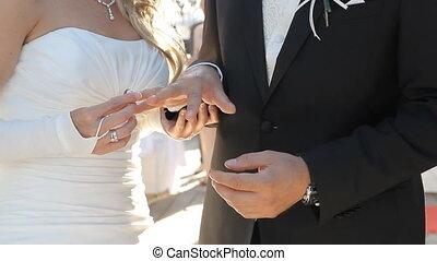 Bride putting a wedding ring