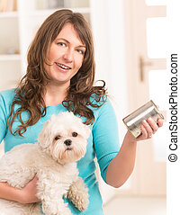Woman feeding her dog - Woman owner of small doggy maltese...