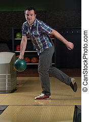 Young Man Bowling - Taking Aim And Getting Ready To Bowl The...