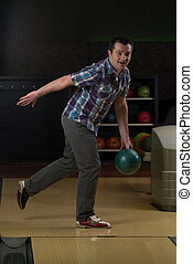 Smiling Young Man Playing With A Bowling Ball - Taking Aim...