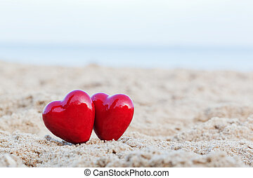 Two red hearts on the beach symbolizing love, Valentine's...