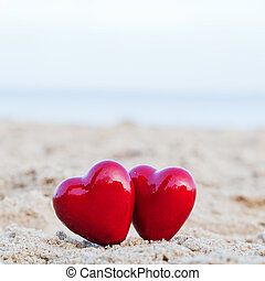 Two red hearts on the beach symbolizing love, Valentines...