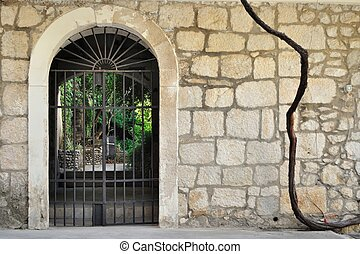Medieval iron gate in stone wall - Medieval iron gate in...